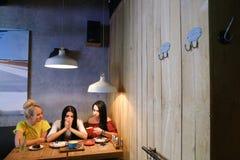 Drei junge nette Mädchenfreundinnen rattern und klatschen, Anteil secr Stockfotos