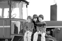 Drei Jungen auf einem Traktor Stockfotografie