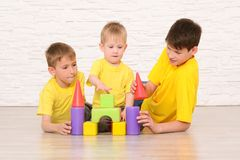 Drei Jungen, die auf dem Boden gegen eine weiße Backsteinmauer spielen stockbilder