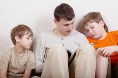 Drei Jungen sitzen und lesen Zeitschrift. Stockfotografie