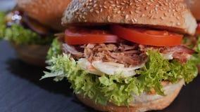 Drei köstliche Hamburger, die auf eine Platte sich drehen stock video footage