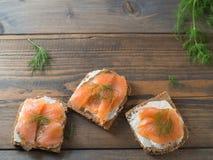 Drei köstliche Sandwiche mit geräuchertem Lachs mit Kopienraum Stockbilder