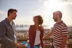 Drei kühle Freunde, die auf einer Brücke lachen stockbilder