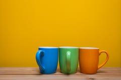 Drei Kaffeetassen auf Holztisch Stockbild