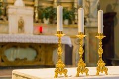 Drei Kandelaber auf dem Altar der Kirche stockbilder