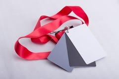 Drei Karten, Weiß, grau und schwarz, auf einem roten Bügel Stockbilder