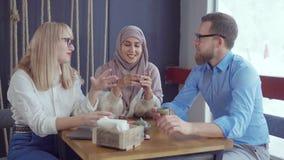 Drei kaukasisch und moslemische Freunde Mann und Frauen sind, trinkend sprechend und Tee stock footage