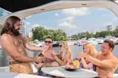 Drei Kerle und zwei Mädchen trinken Champagner auf einer Yacht lizenzfreie stockfotos