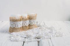 Drei Kerzen auf weißer Tabelle Lizenzfreie Stockfotografie