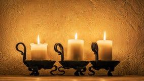 Drei Kerzen, die in der Dunkelheit brennen Lizenzfreie Stockfotografie