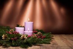 Drei Kerzen in einer Aufkommenblumenanordnung Lizenzfreies Stockbild