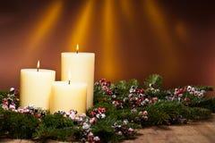 Drei Kerzen in einer Aufkommenblumenanordnung Stockbild