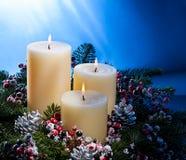 Drei Kerzen in einer Aufkommenblumenanordnung Lizenzfreie Stockfotografie