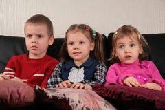 Drei Kinder auf überwachendem Fernsehapparat des Sofas 2 Stockbild