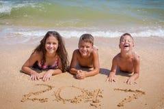 Drei Kinder auf dem Strand mit Zeichen des neuen Jahres 2017 Lizenzfreie Stockfotografie