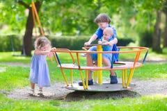 Drei Kinder auf einem Schwingen Stockbilder