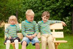 Drei Kinder auf einer Bank in der identischen Kleidung stockfoto