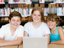 Drei Kinder in der Bibliothek Stockbild
