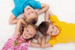 Drei Kinder, die auf den Fußboden im Kreis legen Stockfoto