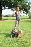 Drei Kinder, die auf einander spielen und stehen Stockfoto