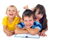Drei Kinder, die auf Fußboden lesen Stockfoto