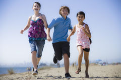 Drei Kinder, die auf Strand laufen Lizenzfreies Stockfoto