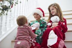 Drei Kinder, die auf Treppe mit Weihnachtsstrümpfen sitzen Stockfoto