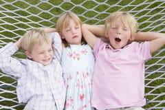 Drei Kinder, die in der Hängematte sich entspannen und schlafen Lizenzfreies Stockbild