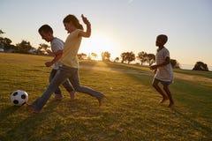 Drei Kinder, die Fußball auf einem Gebiet spielen stockbild