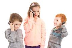 Drei Kinder, die am Kinderhandy sprechen Stockbild