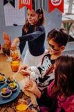 Drei Kinder, die kleine Kuchen beim Haben von Halloween-Partei im Kindergarten essen lizenzfreie stockfotografie