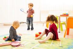 Drei Kinder, die mit Spielwaren spielen lizenzfreies stockbild