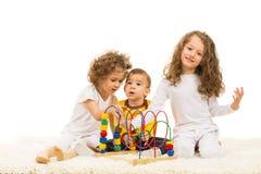 Drei Kinder, die nach Hause spielen Stockbilder