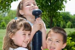 Drei Kinder, die am Park spielen Lizenzfreie Stockfotografie