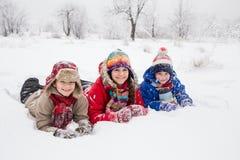 Drei Kinder, die sich zusammen auf weißem Schnee hinlegen Stockbild