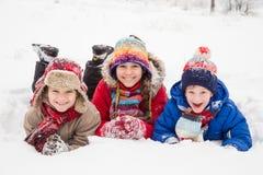 Drei Kinder, die sich zusammen auf Winterschnee hinlegen Stockfotografie