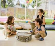 Drei Kinder, die Spaß mit Trommeln haben Lizenzfreie Stockfotografie