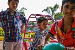 Drei Kinder, die Spiele im Kindergarten am hellen sonnigen Tag spielen lizenzfreie stockfotografie