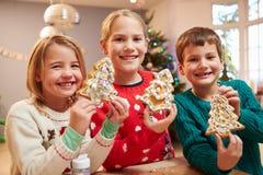 Drei Kinder, die verzierte Weihnachtsplätzchen zeigen Stockbilder