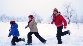 Drei Kinder, die zusammen auf Winterlandschaft laufen stock footage