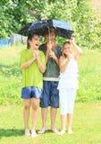 Drei Kinder mit defektem schwarzem Regenschirm Lizenzfreies Stockfoto
