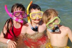 Drei Kinder mit Snorkels stockfotos