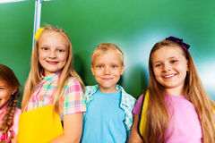 Drei Kinder stehen zusammen nahe Tafel Stockfotografie
