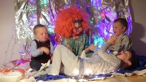 Drei Kinder und ein Clown klatschen ihre Hände stock footage