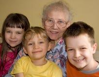 Drei Kinder und Großmutter Lizenzfreies Stockfoto