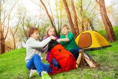 Drei Kinder, welche die Sachen in roten Rucksack verpacken Lizenzfreie Stockbilder