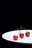Drei Kirschen auf einer Platte Lizenzfreie Stockbilder