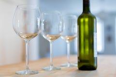 Drei klare Weingläser und eine Flasche gekühltes Weißwein auf a Lizenzfreie Stockfotos