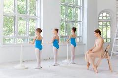 Drei kleine Ballerinen, die mit persönlichem Ballettlehrer im Tanzstudio tanzen Lizenzfreie Stockbilder
