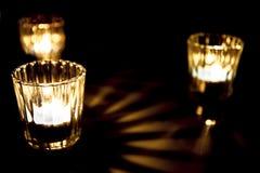 Drei kleine brennende Kerzen auf dem Tisch Stockbild
